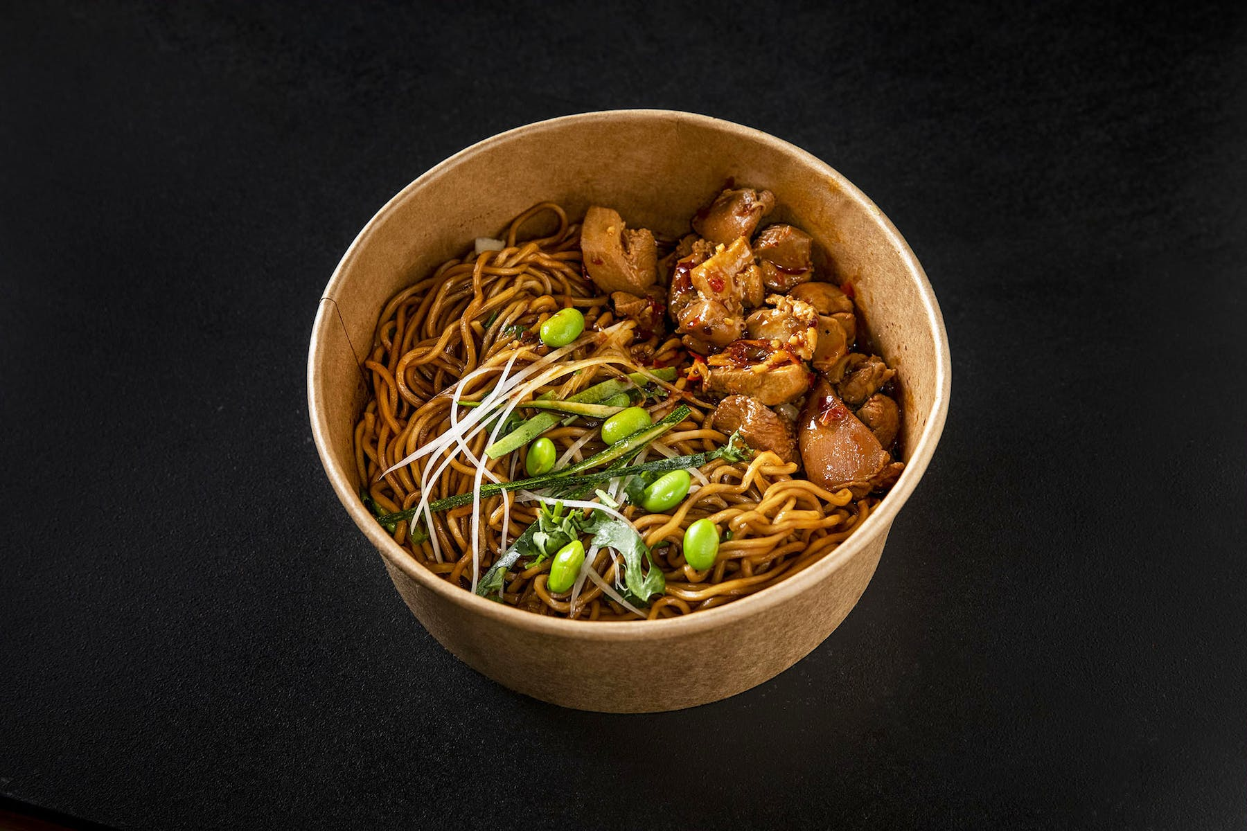 a bowl of noodles topped with veggies