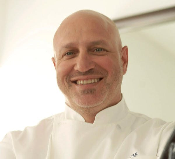 Tom Colicchio wearing a white shirt and smiling at the camera