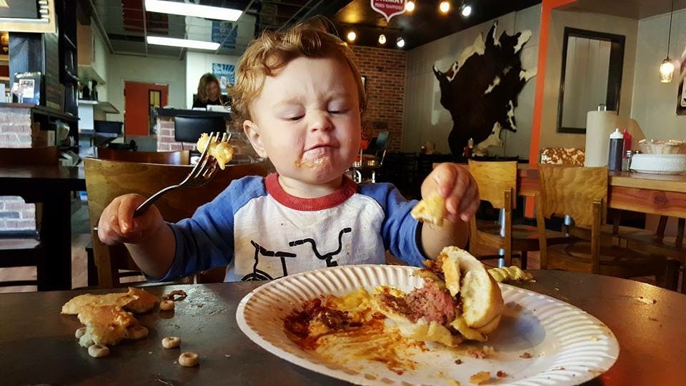 a little boy sitting at a table eating food