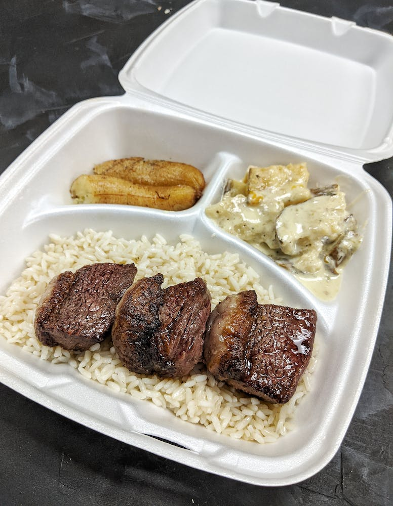 to-go container of steak, garlic rice, au gratin potatoes, and fried bananas from Avenida Brazil