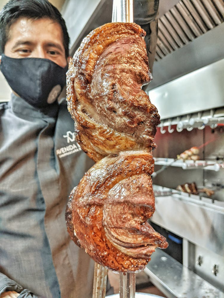 chef with meat on a spit - Avenida Brazil