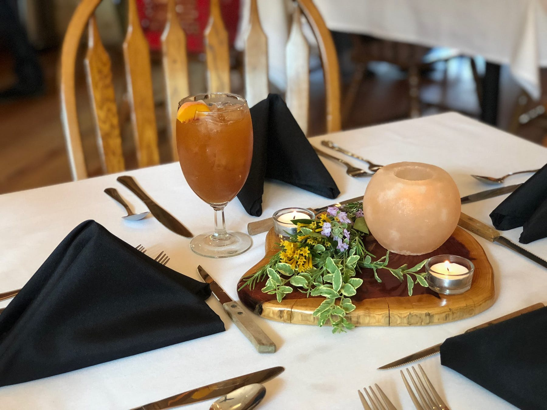 a table topped with silverware utensils and a cup of iced tea