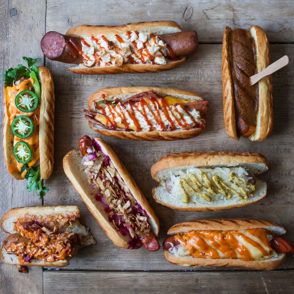 a bunch of hot dogs with different toppings