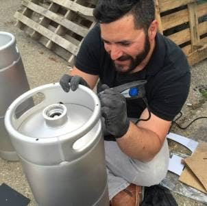 guy who pays the brewery bills writing on a keg of beer