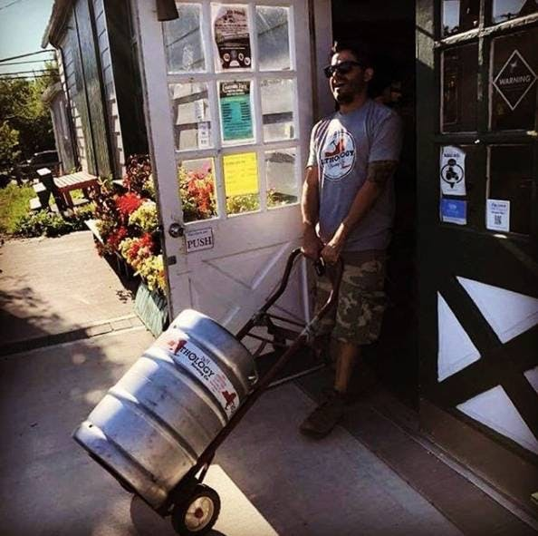 guy wheeling a keg of beer from inside to outside