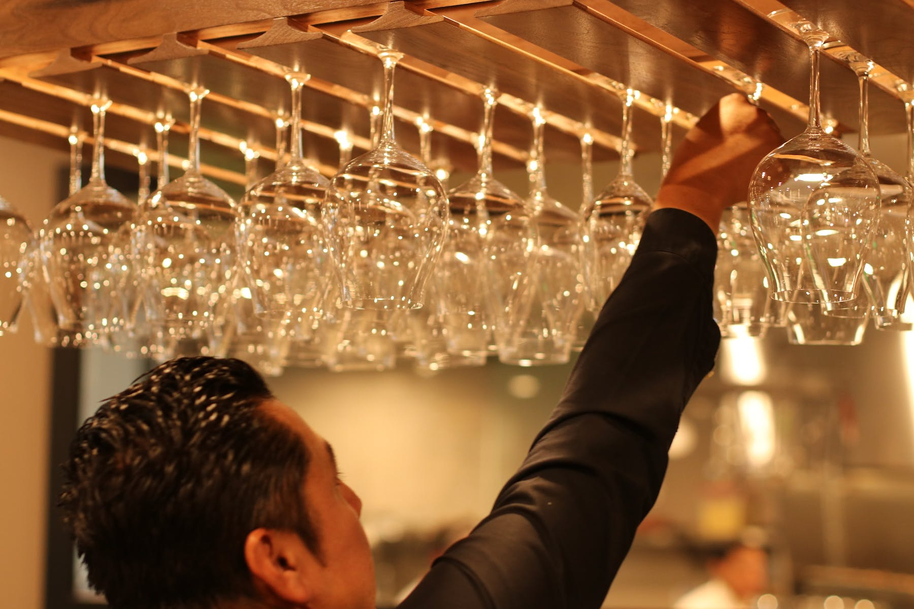 man placing wine glasses in a glass dispenser
