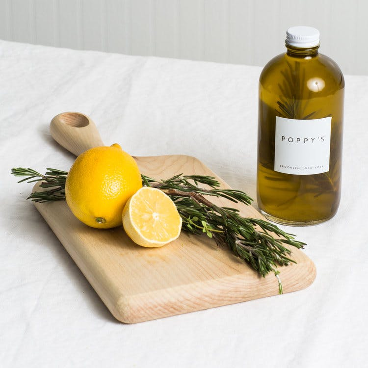 a bottle of olive oil sitting on top of a cutting board