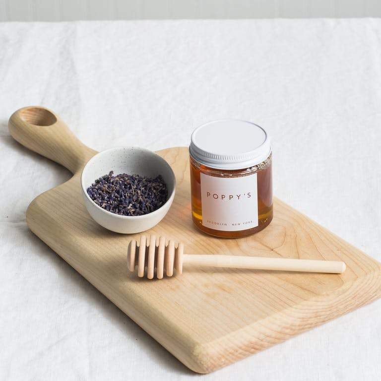 lavender honey sitting on top of a wooden board