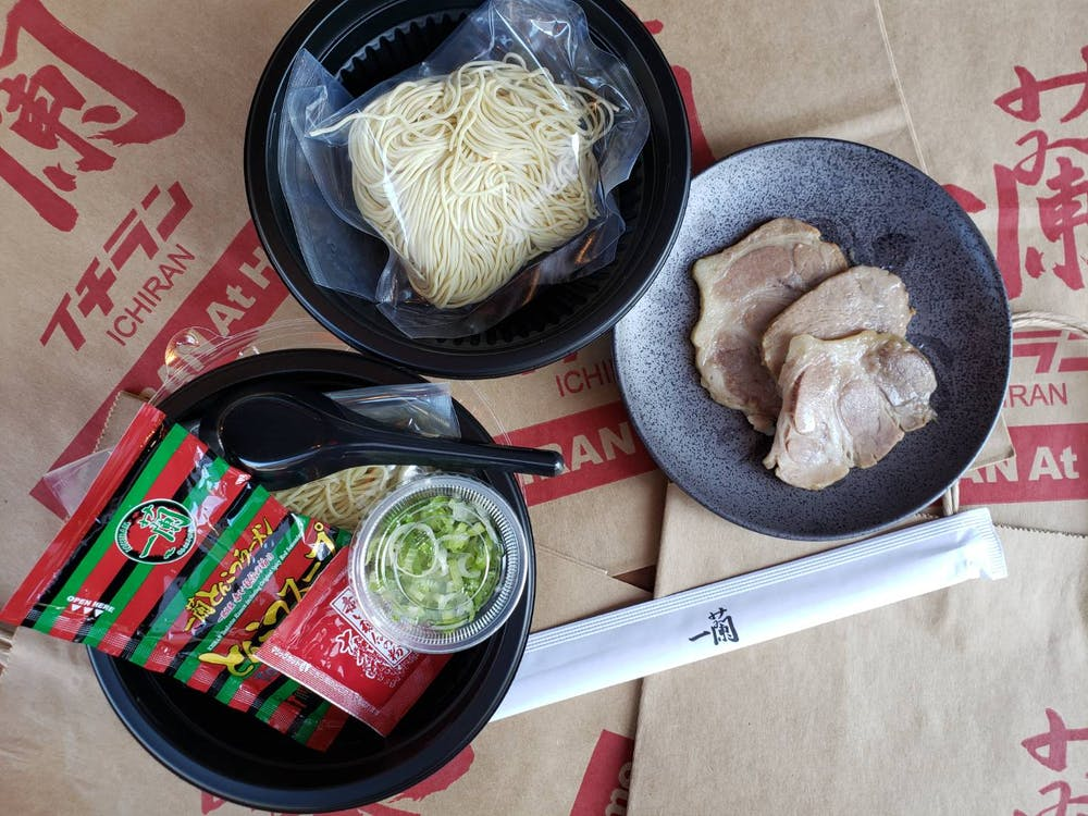 Top view of Fresh Ramen on plates - includes fresh, uncooked noodles, chashu pork slices, scallions, soup concentrate, Original Spicy Red Seasoning, disposable chopsticks, plastic ramen spoon
