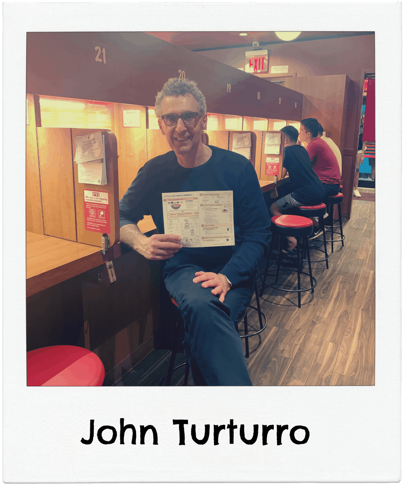 John Turturro sitting in Ichiran ramen