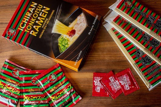 ICHIRAN Take-Home Ramen Kit with contents (noodle packs, soup concentrate, Original Spicy Red Seasoning packs) displayed on top of wooden table