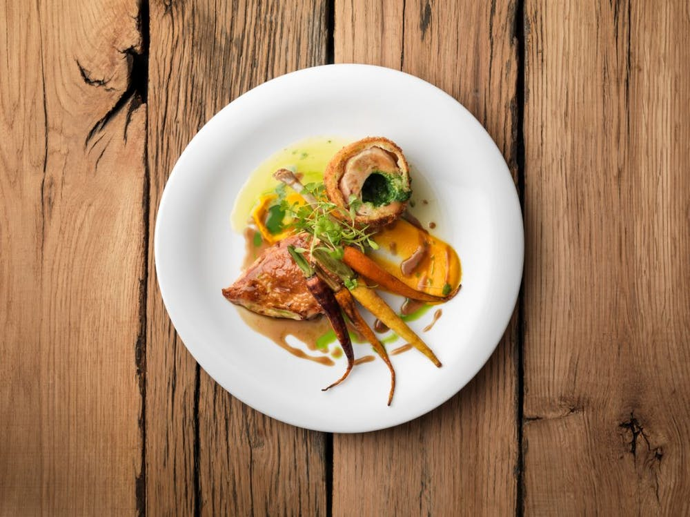 a bowl of food on a plate on a wooden table