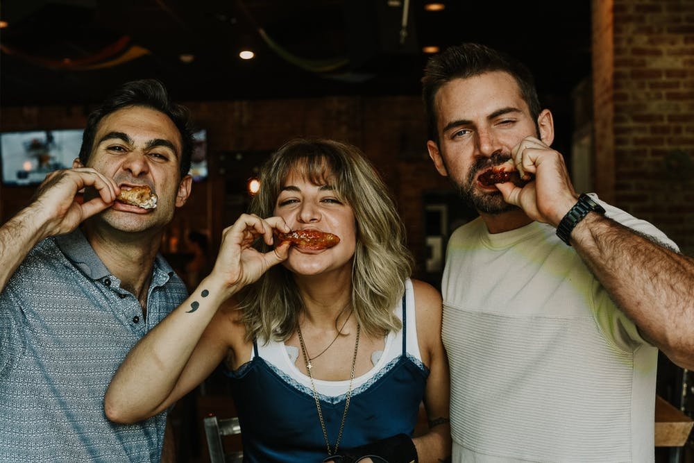 three people eating chicken wings