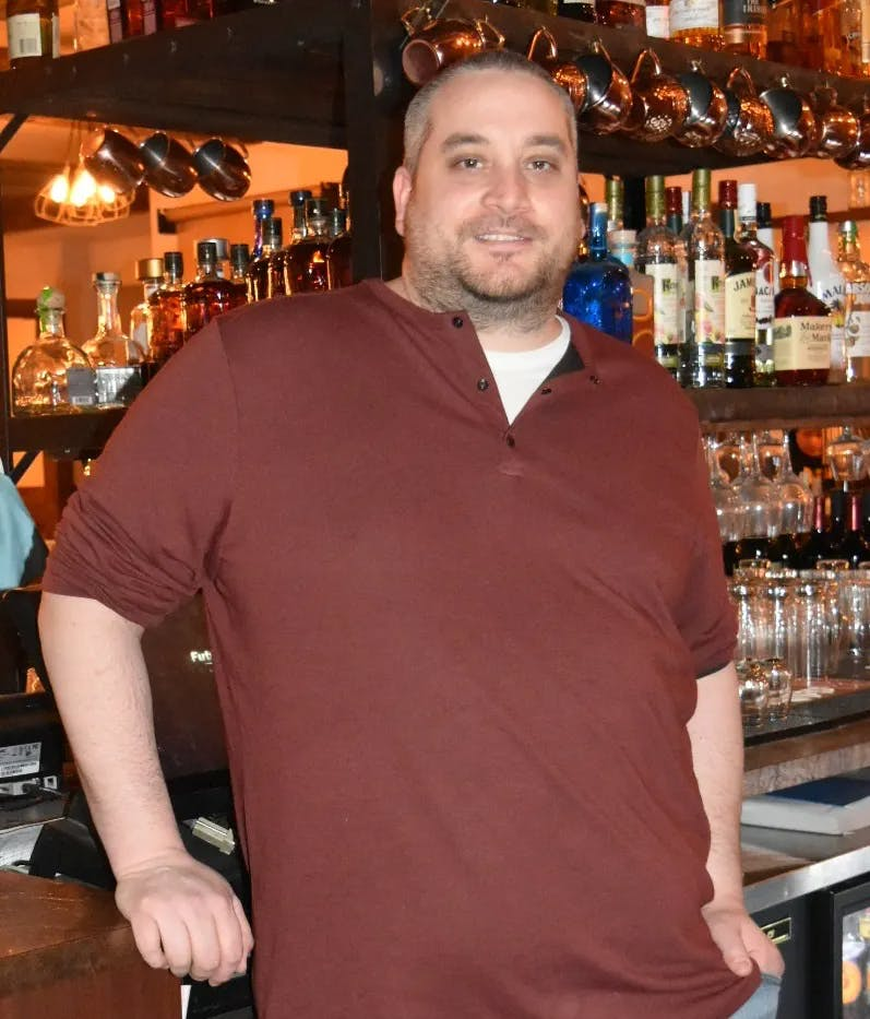 a man standing in front of a bar