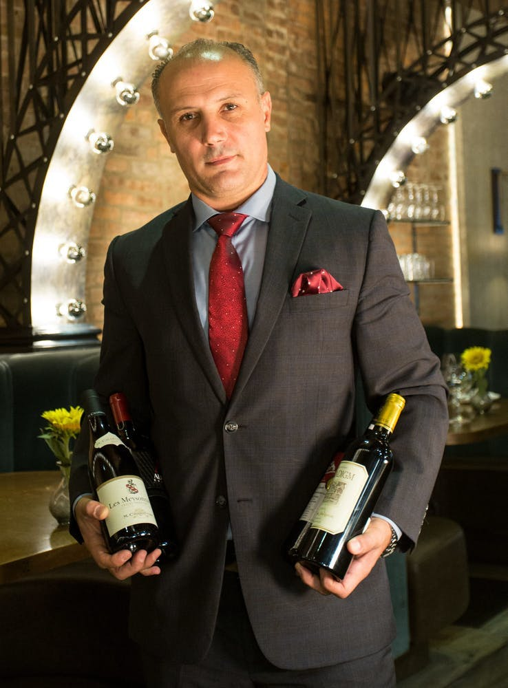 a man wearing a suit and tie holding a wine glass