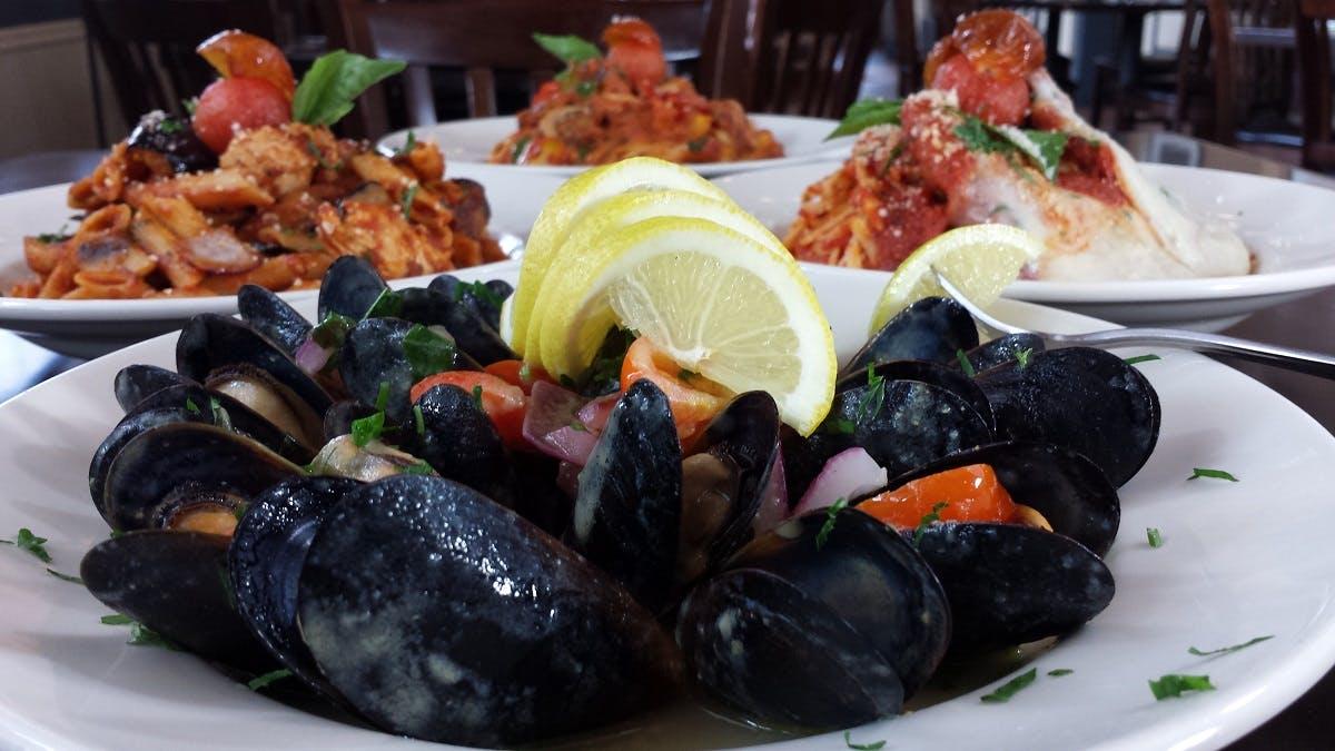 Black seafood dish with lemon slices.