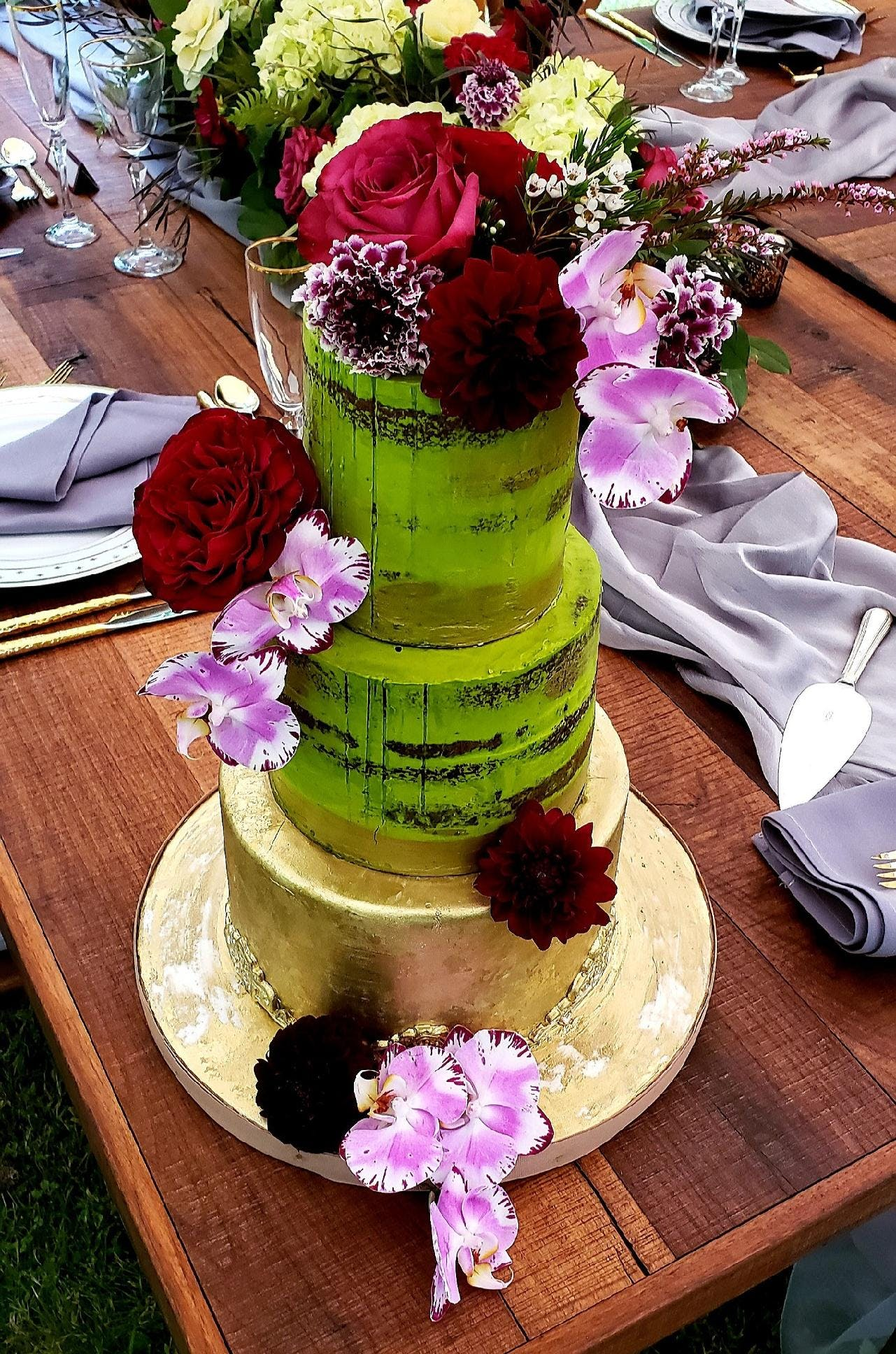 a cake sitting on top of a wooden table topped with a blue flower