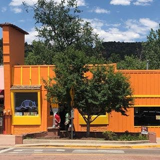 a tree in front of an orange building