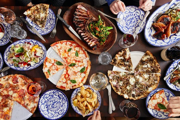 many different types of pizza and grilled mains on a table