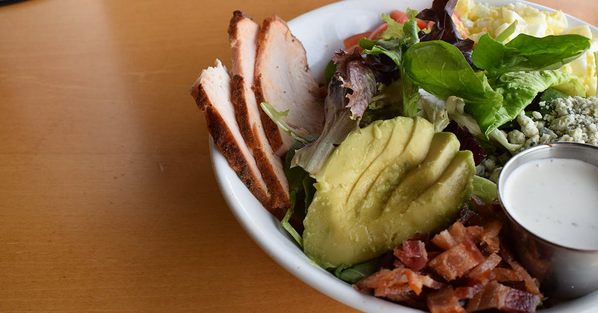 a white bowl filled with chopped avocado, salad and grilled chicken