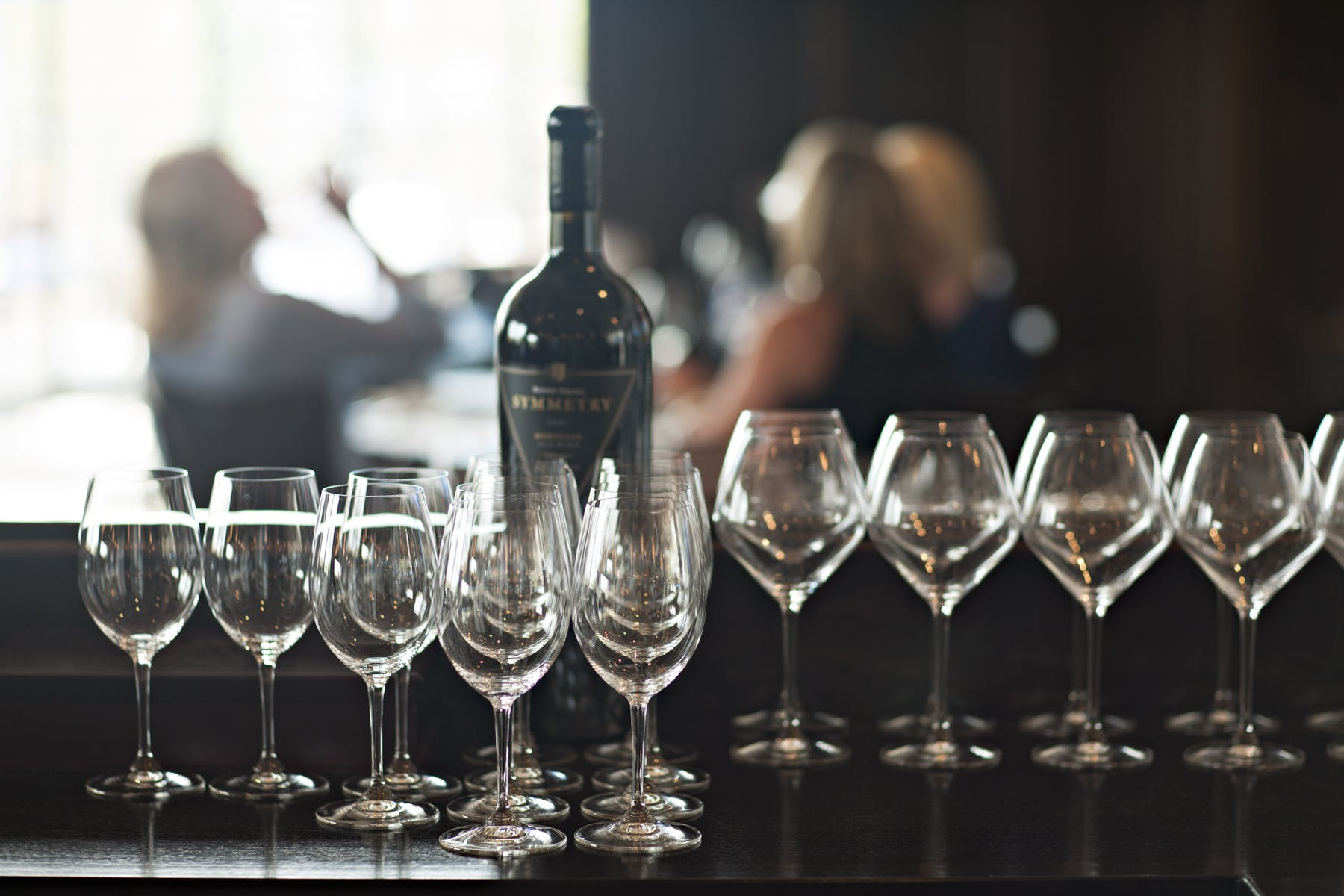 a table topped with a bottle of wine surrounded by crystal wine cups
