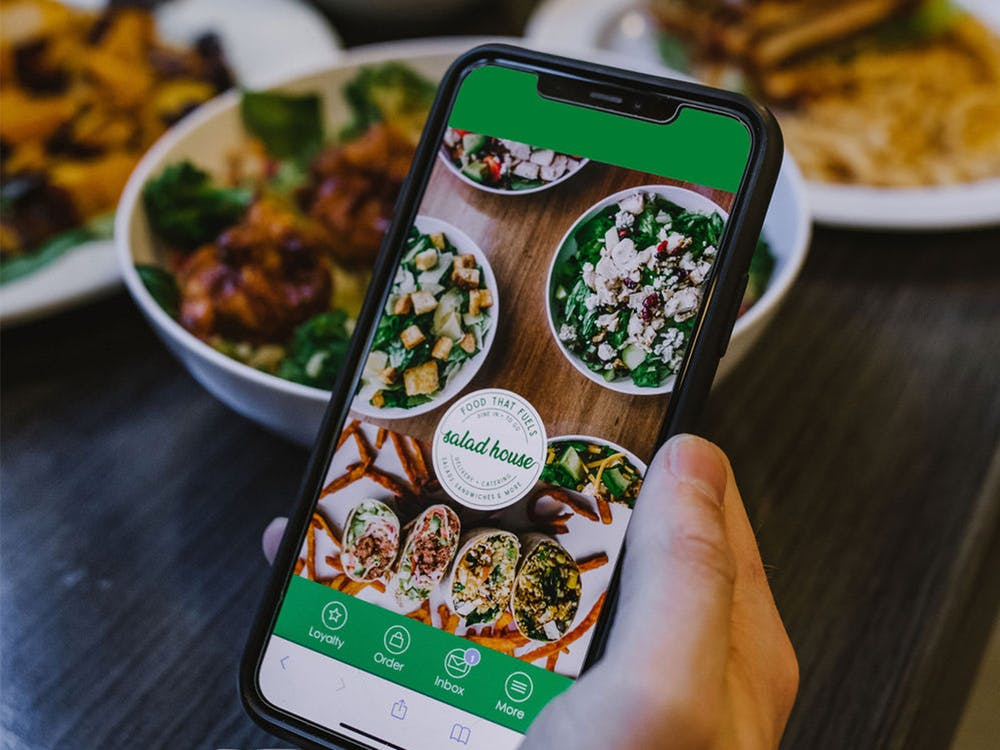 Using The Salad House app to earn rewards and meal discounts.