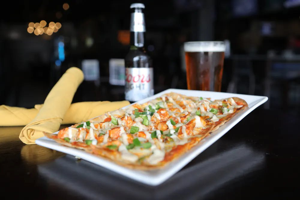 a beer bottle, a glass and a plate of food