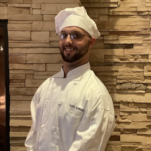 a chef wearing a chef's coat and hat