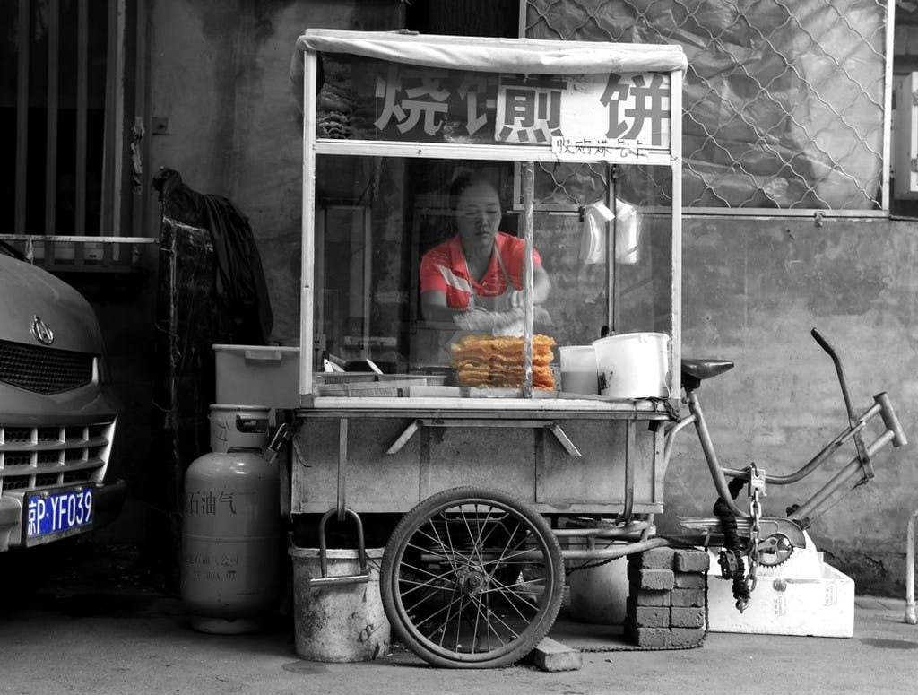 a food stand with a woman standing behind it cooking food