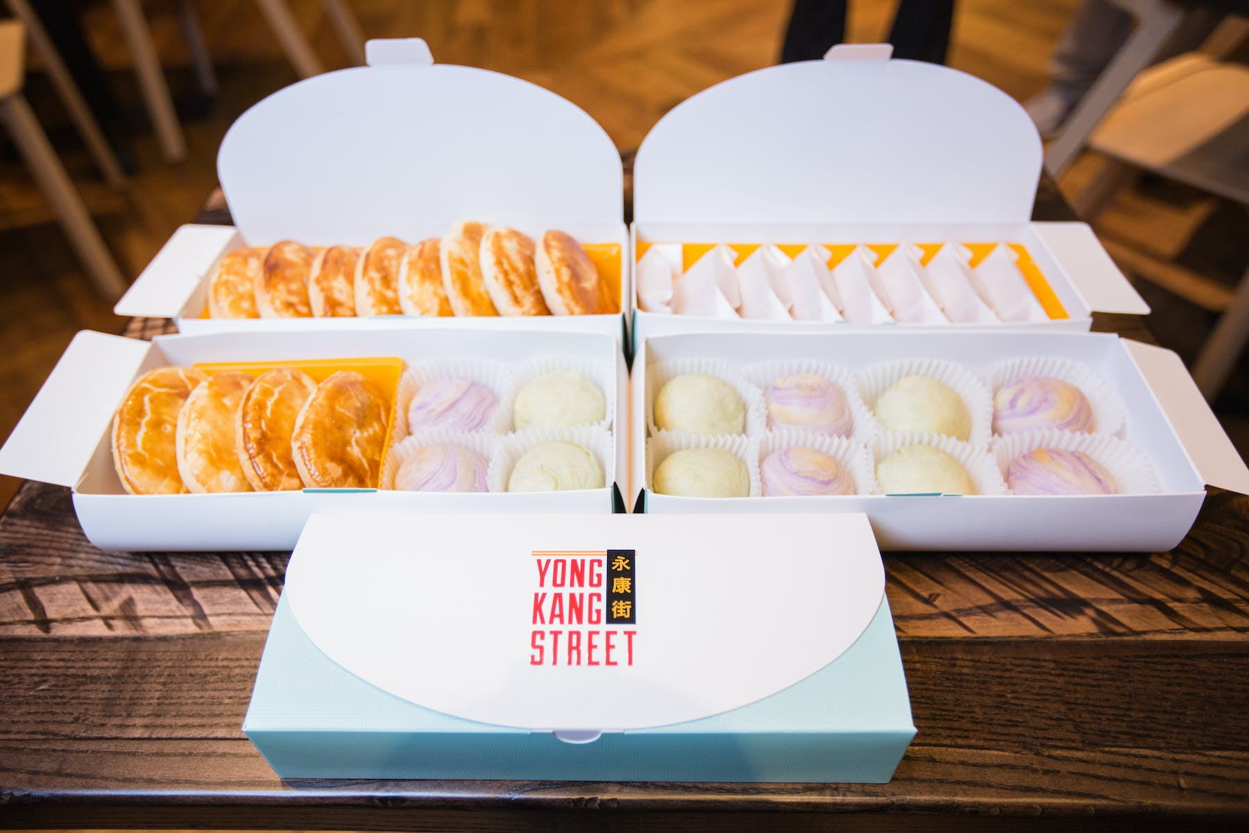 a set of boxes filled with different dumplings and desserts