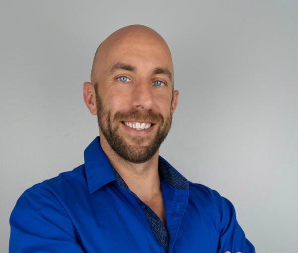 a man wearing a blue shirt and smiling at the camera