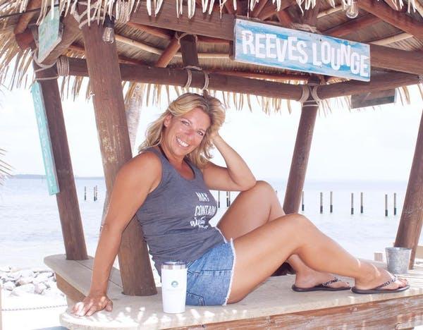 a woman sitting on a bench posing for the camera