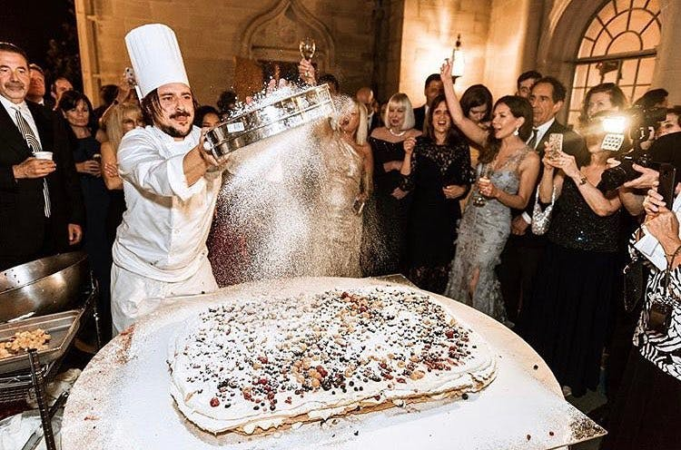 a group of people standing in front of a cake
