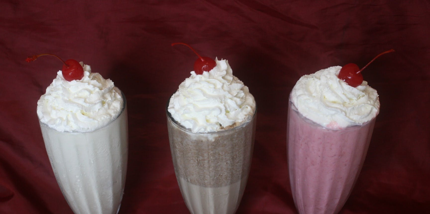 milkshakes with whip cream and a cherry