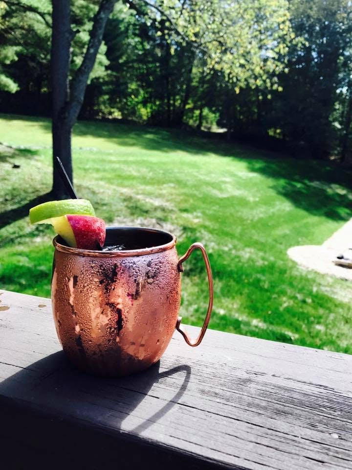closeup of a moscow mule drink with a green field behind it