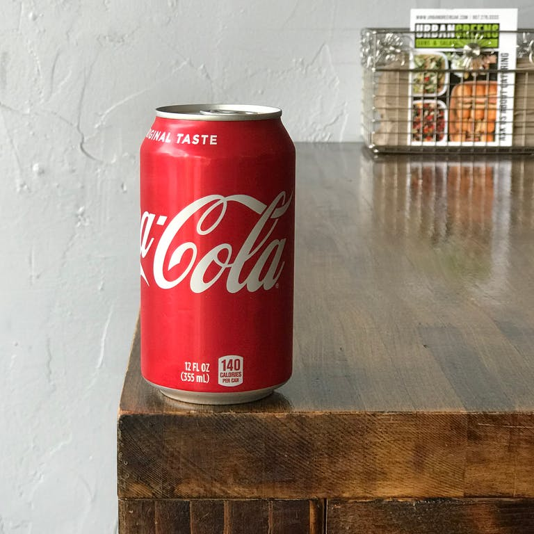 a can of soda sitting on a counter