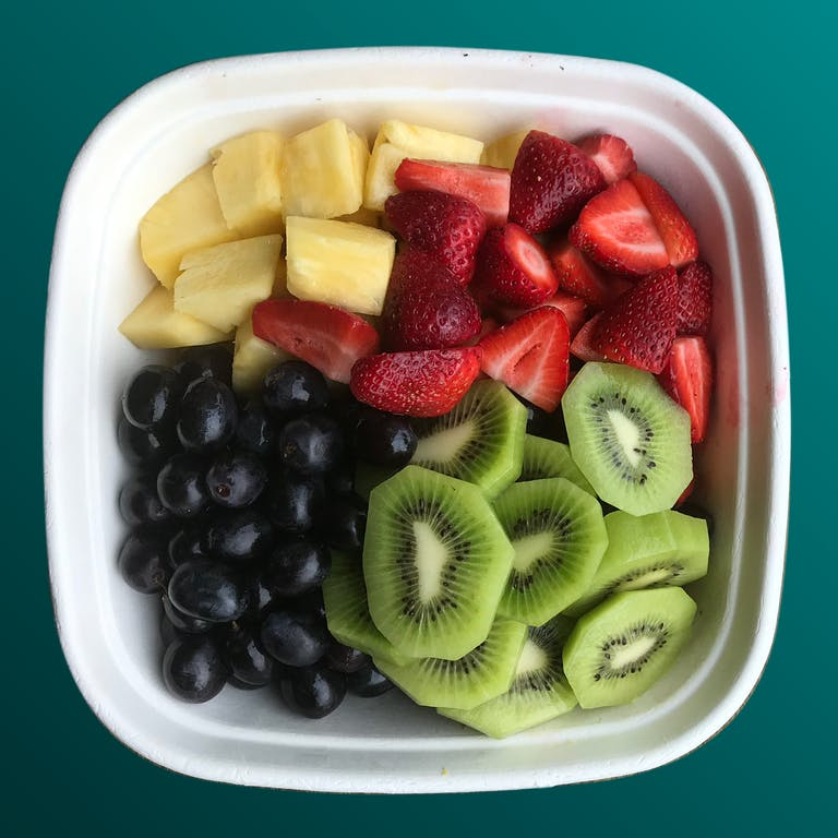 a bowl of fruit with kiwi, banana, strawberry and blueberries