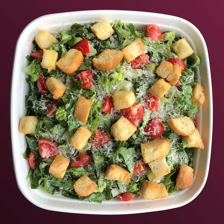 a bowl filled with salad and topped with croutons