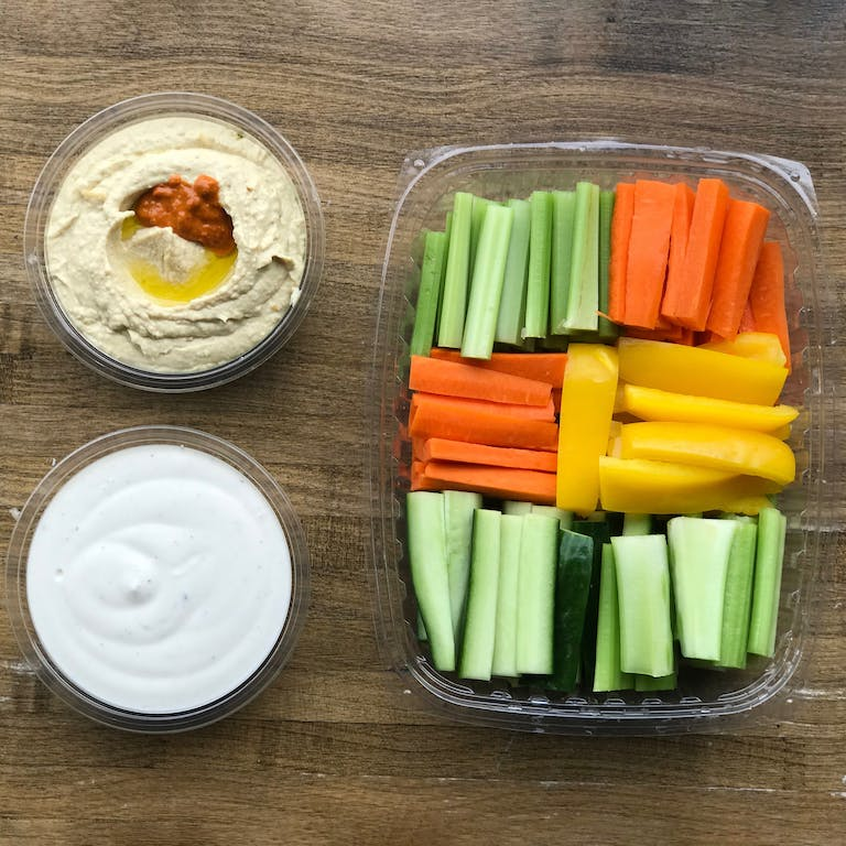 a tray full of veggies sticks and sided by ranch dip