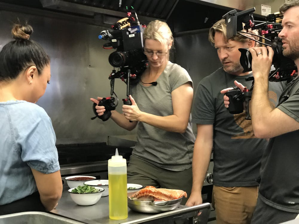 a couple filming a woman talking about food