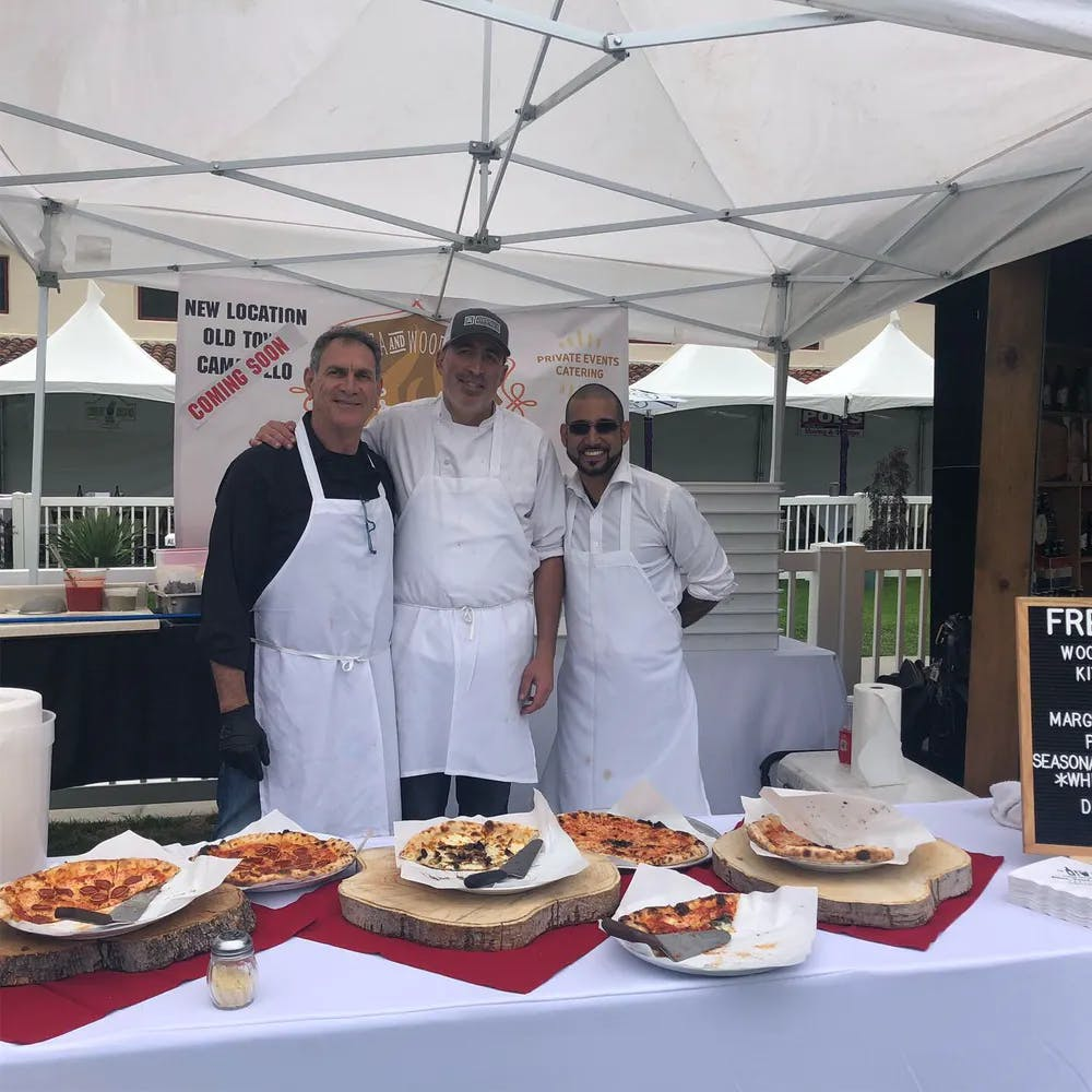 three chefs standing in front of a table with pizzas