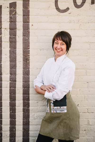a person standing in front of a brick wall - Secret Sauce Food & Beverage Executive Pastry Chef Nadine Donovan