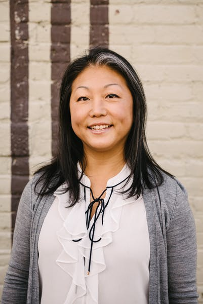 a woman smiling for the camera - Steuben's Uptown GM Yoon