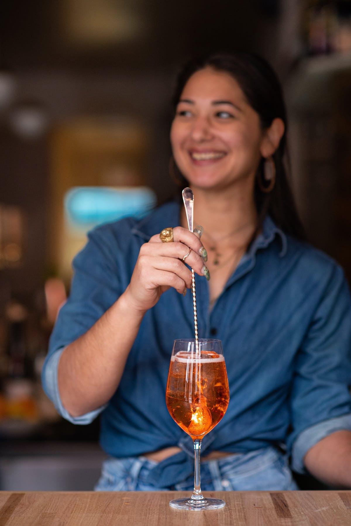 a bartender stirring an Italian cocktail