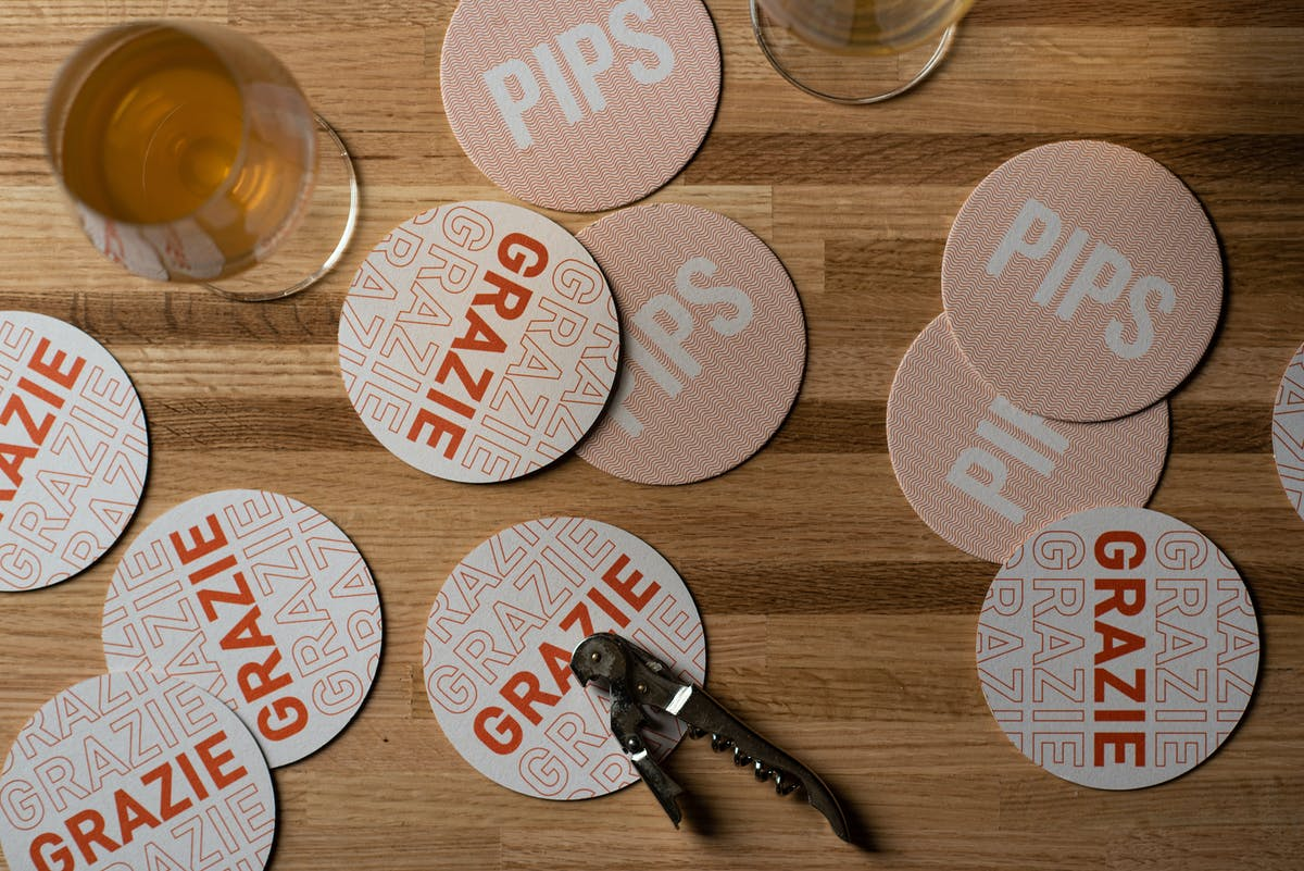 Pips coasters laid out on a table with a wine key
