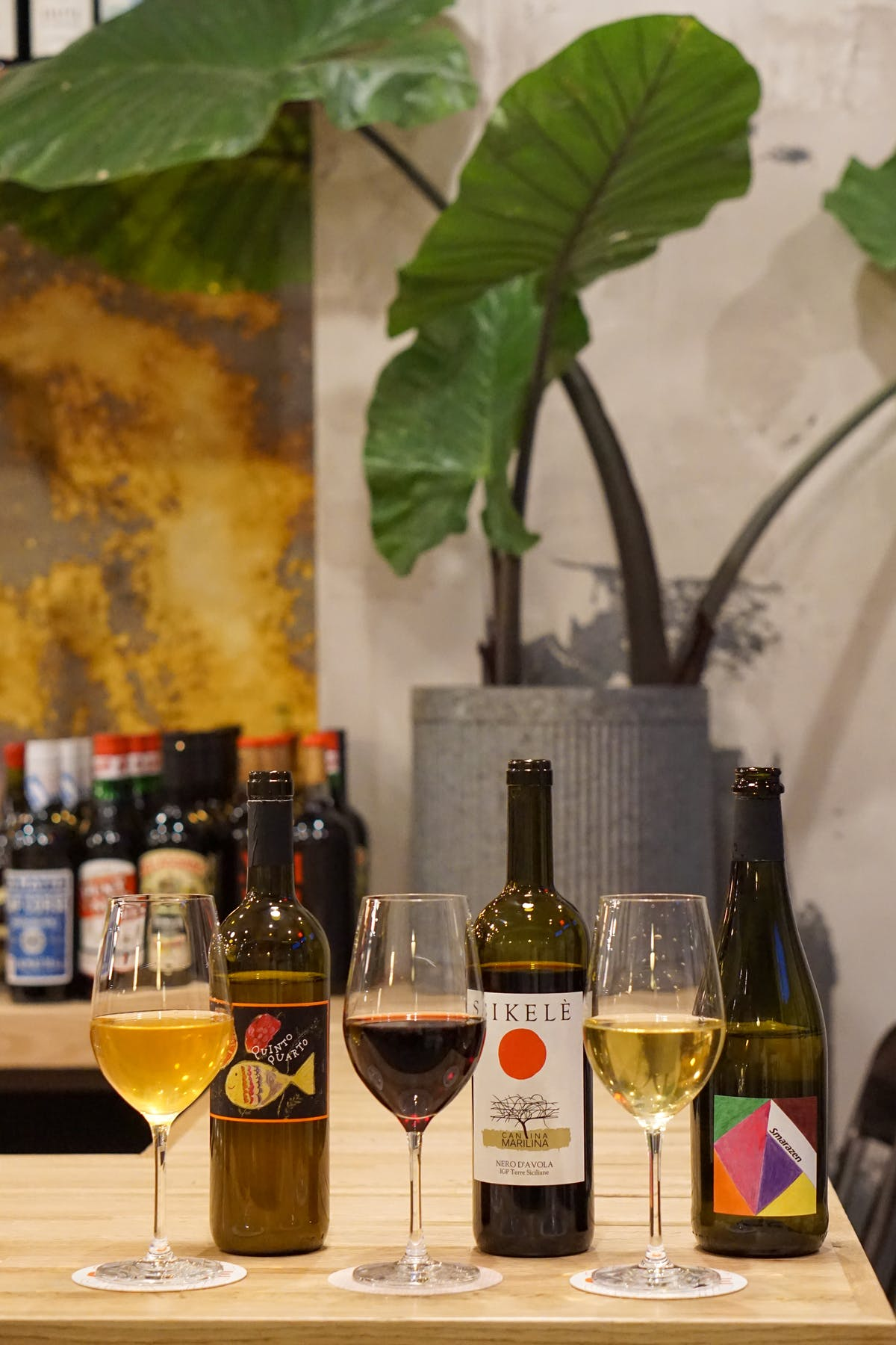 bottles of natural wines next to wine glasses