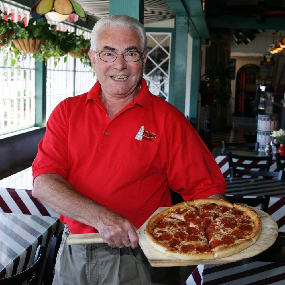 a man holding a pizza on a table