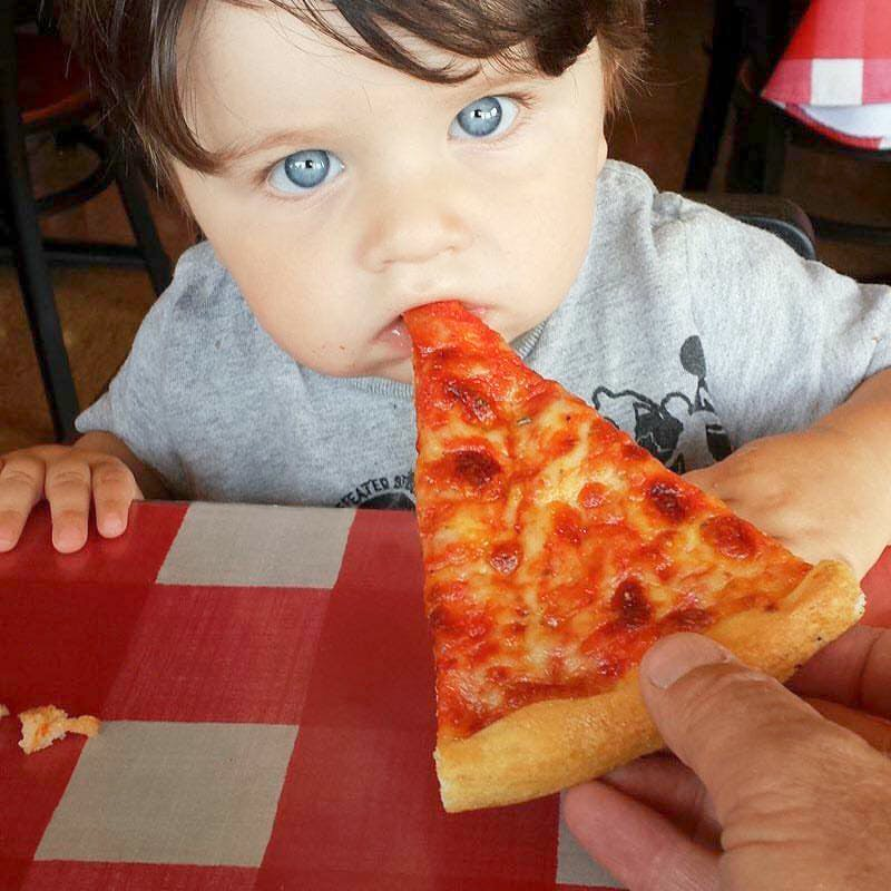 a close up of a child eating a slice of pizza