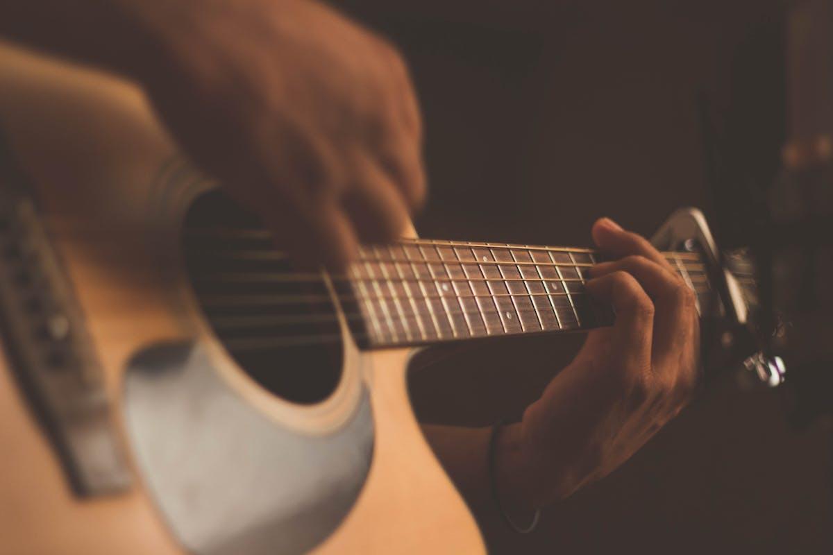 a hand holding a guitar