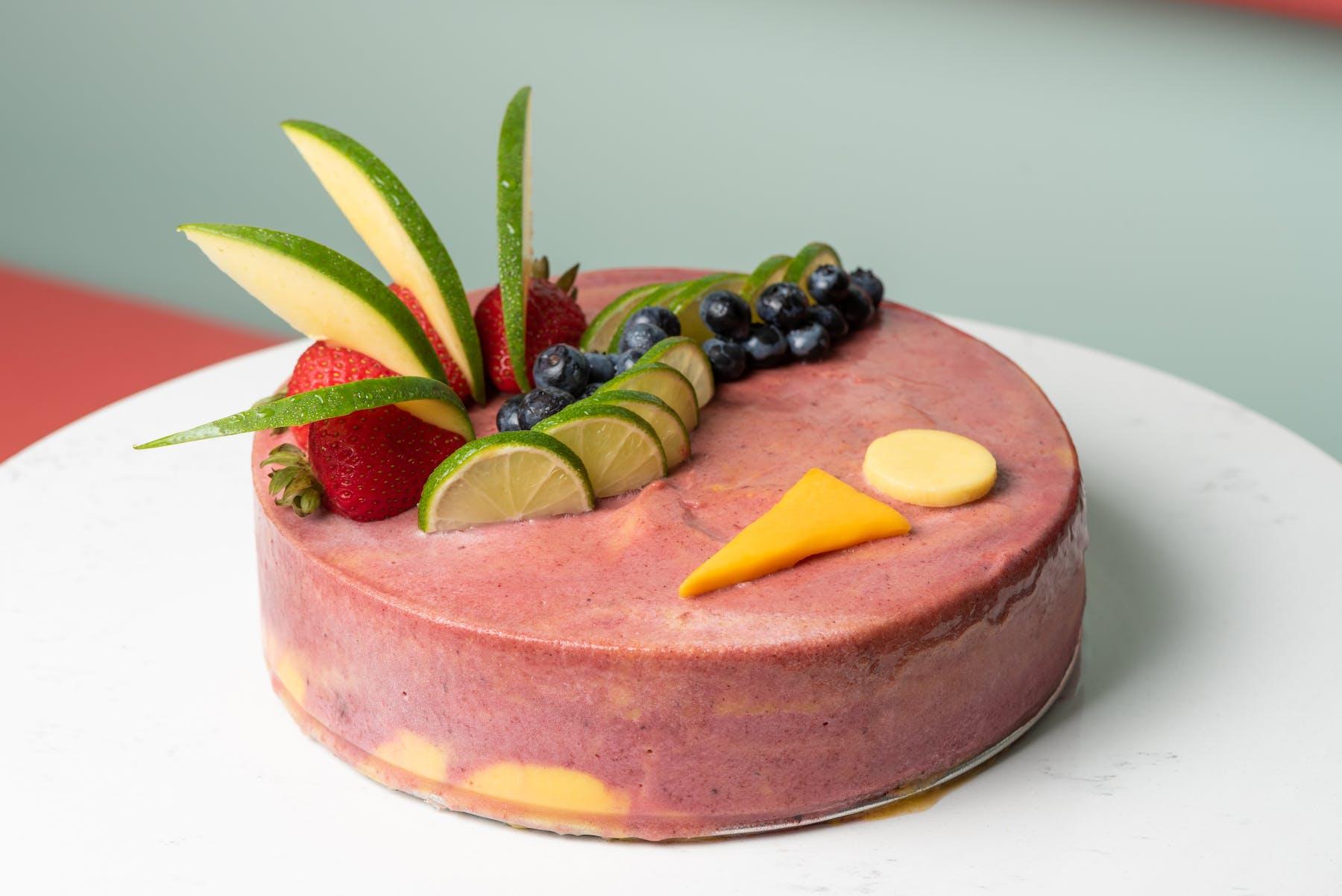 a close up of a pink fruit cake